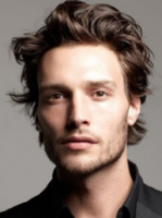 Men light curly hairstyle with medium long length and bangs pulled back.PNG