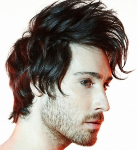 Men trendy hairstyle with long light punky bangs with layers and medium hair length with light wavies.PNG