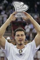 Marat Safin with very short hair holding a glass trophy